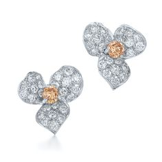 Diamond stud earrings from the Floral Collection in 18K white gold.  Three pave diamond petals frame a champagne diamond center.