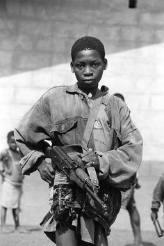 """About 120,000 African children alone are participating in armed conflicts. Some as young as 7 years old. There was a photo of a young boy wearing a tattered shirt that read """"Do more than just watch""""."""