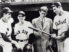 John F. Kennedy looks at a bat with baseball greats, from left, Ted Williams, Eddie Pellagrini and Hank Greenberg in April 1946.