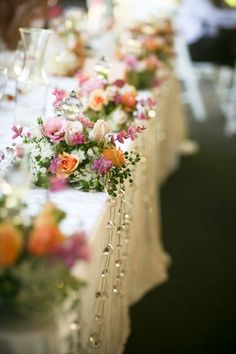 Head table draped in front with strands of beaded garland