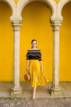 Jennifer Lake Style Charade in a yellow metallic satin pleated skirt, Anthropologie black and yellow ric rac top, 31 Bits woven bag at Sintra, Portugal Yellow Skirt Outfits, Yellow Pleated Skirt, Pleated Skirt Outfit, Metallic Pleated Skirt, Pleated Skirts, Satin Skirt, Yellow Fashion, Colorful Fashion, Accordion Skirt