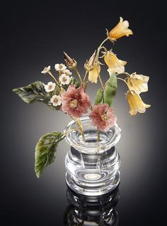 Multi-gemstone Carving of Wildflowers Russia Fabricated in St. Petersburg, this fine quality carving comprises strawberry quartz blossoms, yellow agate bellflowers, and kascholong white opal flowers as well as nephrite leaves, mounted with 18K yellow gold stems, in an optically clear rock crystal vase.