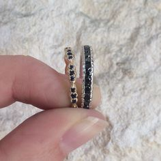 Shaesby wave stack ring in 14k yellow gold with blue sapphires and the textured infinity ring with black diamonds. All handmade in Austin, TX.