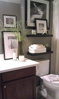 trisha's powder room ~Love the Bathroom shelving. What I like is the rich & warm color of vanity cabinet with clean white top, toilet & trim. Composed and reliable Gray walls.