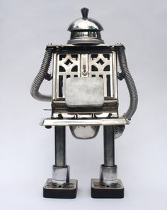 Made out of found objects. Measure 17.25 inches high. Eyes and mouth light up red and green, powered by two AA batteries inserted into the pack on his back (batteries not included) Switch is located on back.