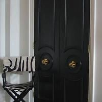 Ferreira Design - entrances/foyers - glossy black doors, black doors, gray tile, white walls, glossy black double doors, antiqued brass hardware, brass hardware, antiqued brass door knobs, zebra print directors chair, directors chair, bi fold doors, black bi fold doors,