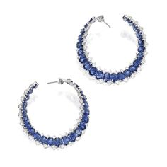 Pair of 18 Karat White Gold, Sapphire and Diamond Earrings. The hoop-style earrings set with 46 oval-shaped sapphires weighing 42.06 carats, framed by round diamonds weighing 7.50 carats