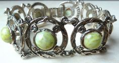A Vintage Celtic style panel bracelet. The bracelet is made in a silver tone metal with eight panels.  Each panel has a centrally set green faux connemara marble stone. The bracelet measures approx 18.5cm.  It has A lovely vintage piece circa late 1980's - 90's.