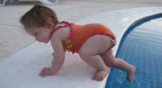 Una niña entra en la piscina