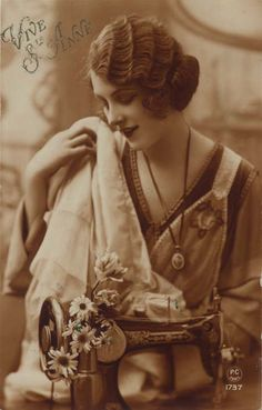 Vintage sewing postcard - lovely lady posing with sewing machine.