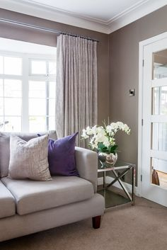 Grey sitting room with silver and purple accents; cartridge pleat curtains