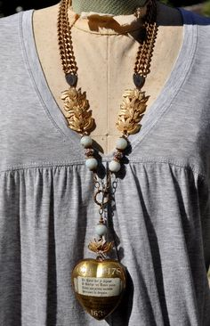 This one-of-a-kind Congres Marial assemblage necklace, in soft tones of gold and pale blue, features an antique French ex voto sacred heart reliquary locket / prayer box. It measures approximately 2 3/4 x 2 (7cm x 5cm) and opens up into two sections. This golden gem, and others like it, were created to celebrate a historic religious event in which King Louis X111, in the year of 1638, consecrated his person, crown and subjects to the Virgin Mary. Copies of his oath and a prayer were...