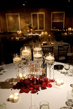 Lovely candle clusters.  Centerpiece of floating candles or pillars and 3 groups of 3 glass votives to complete the tablescape. Elegant. Simple. Inexpensive.  Use white for contemporary, classic ivory for conservative, or choose the perfect match to your wedding colors.  BeverlyHillsCandle.com