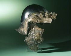 Roman iron cavalry helmet 150 - 200 CE. Forehead band is decorated with oak-leaves (corona civica) and laurel-leaves. Left cheek is missing, right cheek is decorated with a horse and rider. An inscription on the cheeks identifies the owner: 'VANNI'. Found in the Netherlands, Gelderland, Nijmegen