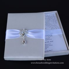✨So beautiful!!! Ivory silk box adorned with white ribbon and dangling crystal brooch. Letter press invitation card✨   See more at www.boxedweddinginvitations.com   #wedding #invitation