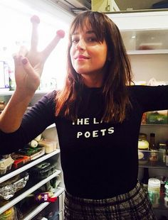 Dakota Johnson in a particularly wonderful example of a Bella Freud jumper. Text reads: 'The Lake Poets'. Nice.