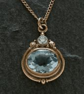 James Meyer. Pendant-R: Cast, forged and fabricated pendant in 18k yellow gold with a cabochon top faceted bottom aquamarine in a 22k millegrained bezel and set with a diamond. The piece also has engraved swirl motif.