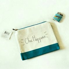 """Chic happens blue & beige canvas zip pouch NWT """"chic happens"""" phrase zippered pouch in dark teal blue & oatmeal beige. Brand new w/ tags. 6"""" tall x 7.5"""" long. Use this little beauty as a clutch, makeup bag, or fill with whatever sparkly things your heart desires. <3 Bags Cosmetic Bags & Cases"""