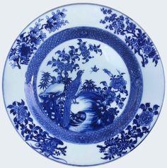 Assiette à décor en bleu sous couverte à décor d'un paon en porcelaine de Chine de la Compagnie des Indes d'époque Yongzheng Peinte en bleu sous couverte, à décor sur la bassin d'un paon parmi des rochers et des plantes.