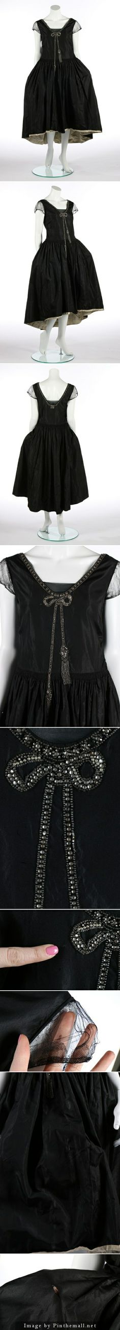 A black taffeta robe de style, circa 1926. with rhinestone and seed-beaded trompe l'oeil bow to the bodice front, shirring to waist, tulle puff sleeves, the hem faced in ivory taffeta, with integral black taffeta hooped panniers. KTA