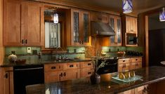 mission style kitchen decorating - green accents and oak cabinets with dark metal hardware