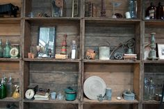 An entire wall created of stacked wooden crates contains various antique objects.