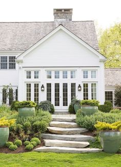 Stunning white home exterior with paneled glass windows, gray roof and stone slab stairs leading to the lawn below.
