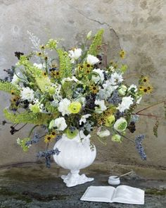 "Dramatic welcome arrangements catch guests' attention and invite them to sign in. To reach great heights, pair tall vessels with long-stemmed flora. This burst of bayberry, foxtail lily, green pokeweed, and cosmos is filled out with ranunculus and lisianthus. For a displayable keepsake, let friends write well-wishes in gold-paint pen on a ceramic guest book. The Details: Astier de Villatte ""Citrouille"" vase and open book (astierdevillatte.com for stores)."
