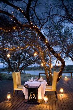 Love the twilight hurricanes on the deck and dangling from the trees; and especially the White twinkle lights on the tree trunks and branches.