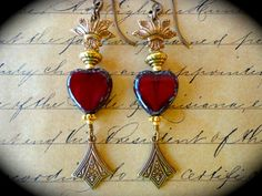 Flaming Milagros ~ Deep red Czech heart beads are topped with flames in painted brass charms in bronze & sealed. Romantic, passionate...