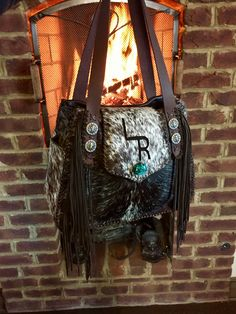 A Bonnie Bag with the owners brand in brown suede with a turquoise stone on the flap. Side pockets lined in suede and straps with hand cut fringe and cross conchos finish off the bag This bag is lined with two interior pockets. gowestdesigns.us