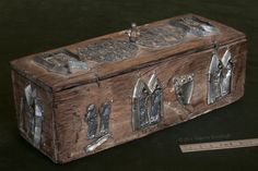 Late 14th to early 15th century. Wooden box with tin alloy badges, 8 (with bead 10.3) x c.24.5 x 9.3 cm Found inside the Châsse Nôtre-Dame in 1856. Tournai, treasury of the Cathedral of Nôtre-Dame.