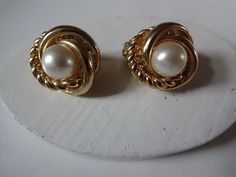 Vintage Gold Tone Knot Clip Earrings with Center Pearl.  Beautiful pair of clip earring with center simulated pearl. Rings of gold surround this pearl, one twisted and two smooth. A classic pair that