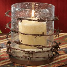 Wrap some rusty barbed wire around a glass candle holder and you get instant gorgeous.......D.