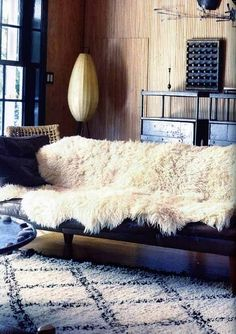 Cozy up your sofa by draping a sheepskin rug over it.