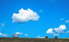 青空の下、トラックと牧草ロール