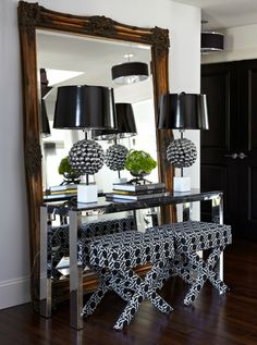 Atmosphere Interior Design  Modern foyer entrance with ornate floor mirror, polished chrome console table, white & black X ottomans and metal lamps with glossy black vinyl lamp shades.