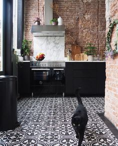 Black kitchen cupboards I brick wall I black and white tiles