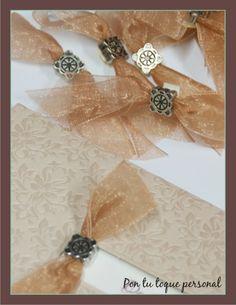 Invitación de boda alargada con adorno de metal y plano. Detalle de los lazos y los adornos de metal.