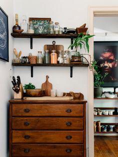 Dettaglio cucina con cassettiera dal sapore antico e mensole in legno scuro abbinate. Il tutto risalta molto bene grazie alla parete molto chiara, leggermente colorata.