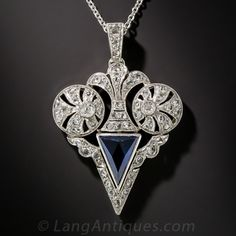 From early twentieth century France, an exquisitely and distinctively designed sapphire and diamond pendant, hand crafted in platinum over 18K gold. A dark midnight blue faceted triangular sapphire, weighing just a shade over a carat, is crowned by a stylized fleur-de-lis flanked on each side by mirror image circular motifs, all aglitter with tiny twinkling rose-cut diamonds. A one-of-a-kind wonder jewel made before 1912. The pendant measures 1 3/8 by 7/8 inches and is strung on a d...