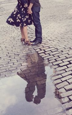 great pose using reflection of a couple in puddle