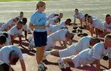 SSgt. Dawn Adams (standing), a military training instructor with the 331st Training Squadron at Lackland AFB, monitors trainees' pushups during physical readiness training.
