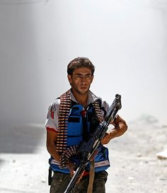 Dust and smoke surrounds a Free Syrian Army fighter after a tank shell exploded