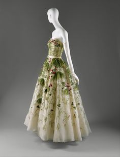 """Dior """"May"""" dress, circa 1953.   Dior reveled in the paradox of the natural and the sophisticated. In """"May,"""" flowering grasses and wild clover are rendered in silk floss on organza. This """"simple"""" patterning of meadow-gone-to-weed is composed of the tiniest French knots and the meticulously measured stitches of the hand embroiderer."""