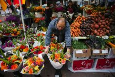 Xe Chang from Mee Gardens organizes his fliwers before the opening of the Ballard Farmers Market   Marcus Yam/Seattle Times