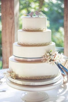 - 4-tiered wedding cake with bird cake toppers, decorative piping detail, flowers, ivory and navy ribbon and brooch details