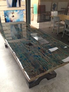 Tabletop of reclaimed wood moulded with transparant colour coating.  Learn more at www.epoxyflooring.info