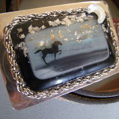 A lone stallion under a star spangled sky. This is one of my fused glass pieces used as a centerpiece for a modern statement buckle. The stars are