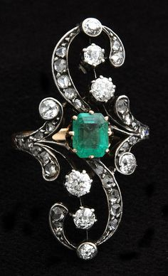 """From Russia and circa 1890, this is an emerald and diamond dress ring. The central trap-cut (also known as """"step-cut"""") emerald is set in 18k..."""